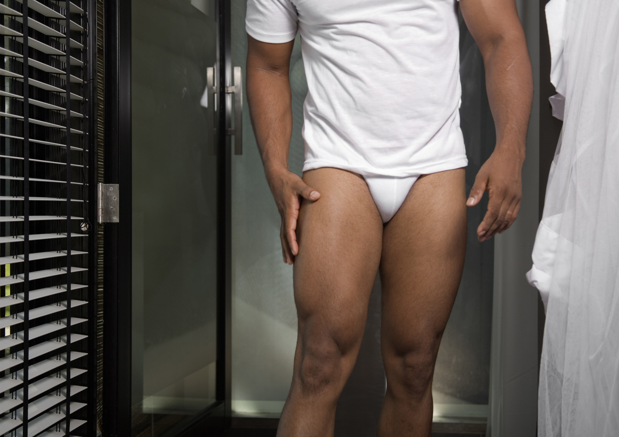 A young man seen from chest to knee walks out of the bathroom toward camera. He is wearing a white tee and briefs