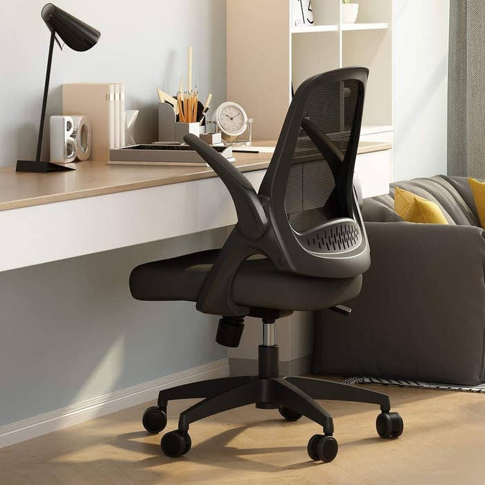 desk chair pulled up next to desk with arms adjusted for appropriate height