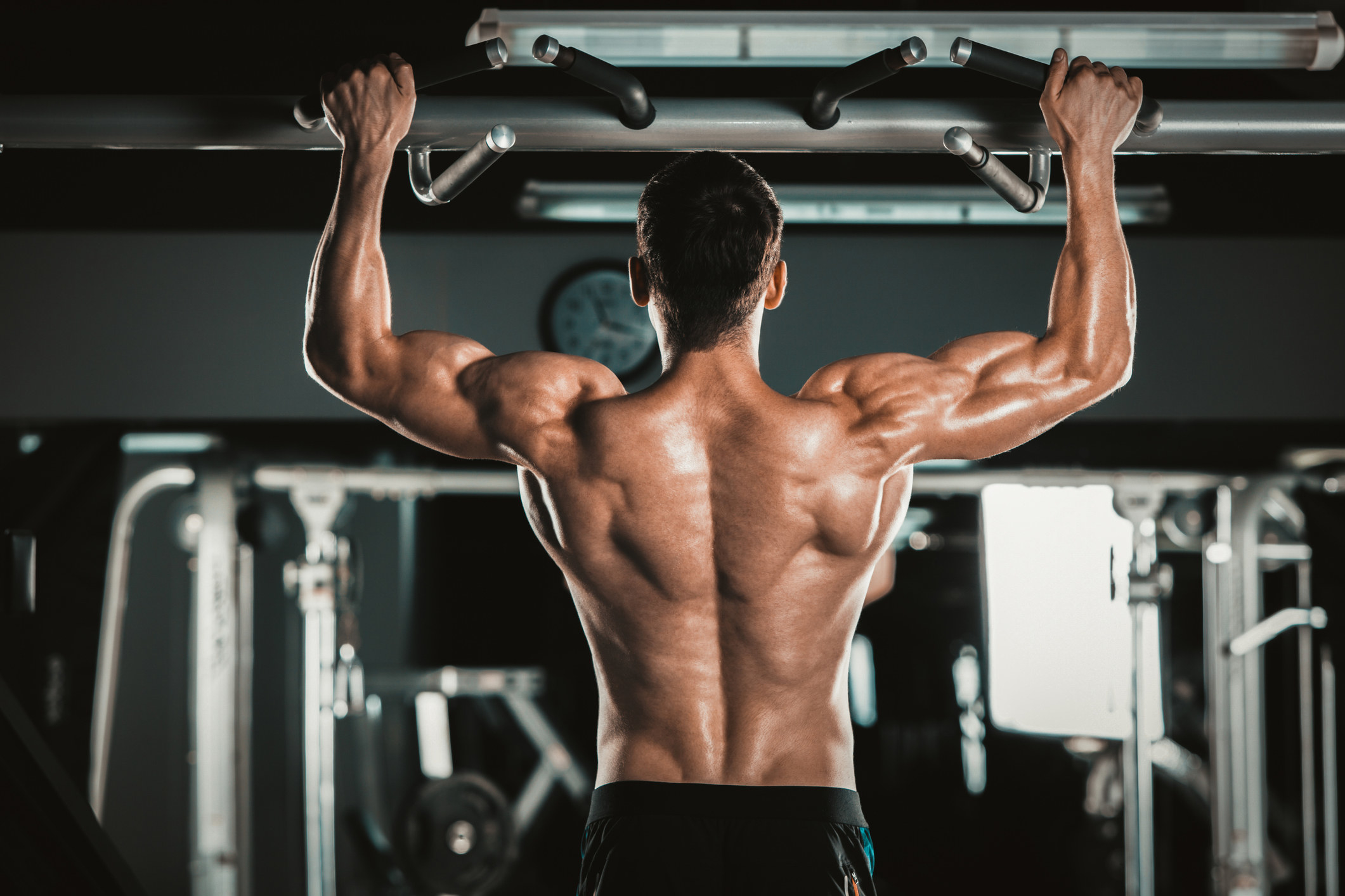 Muscular fitness male model pulling up on horizontal bar in a gym