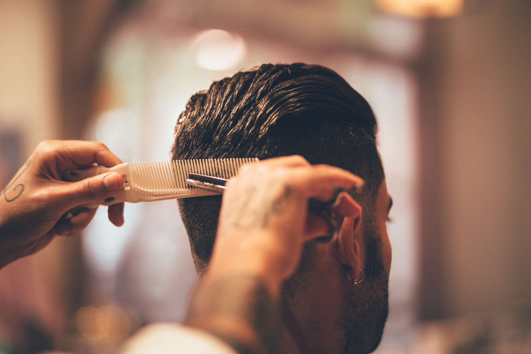 Close-up of barber's tattooed hands holding comb and scissors and giving man haircut