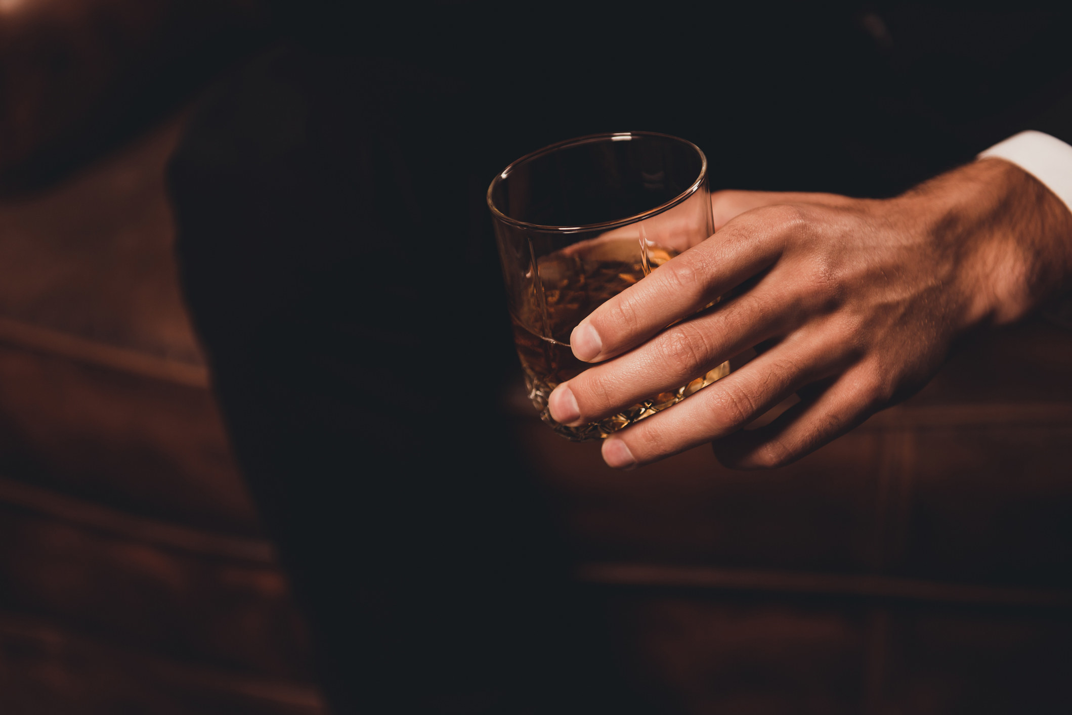 Close-up of man's hand holding class of whiskey