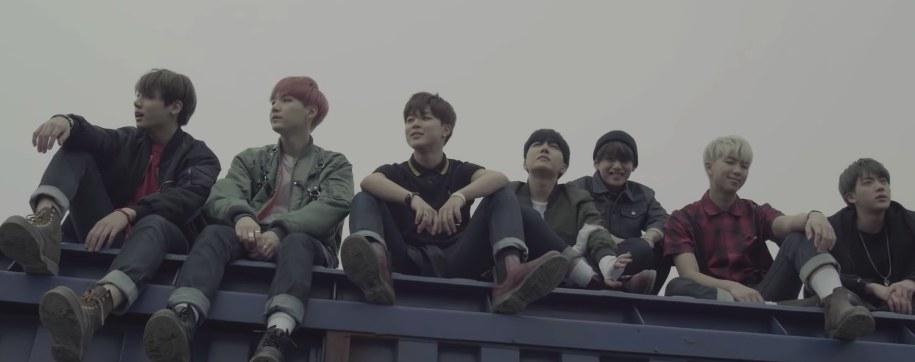 BTS sit in a row on top of a train car in the I Need U music video
