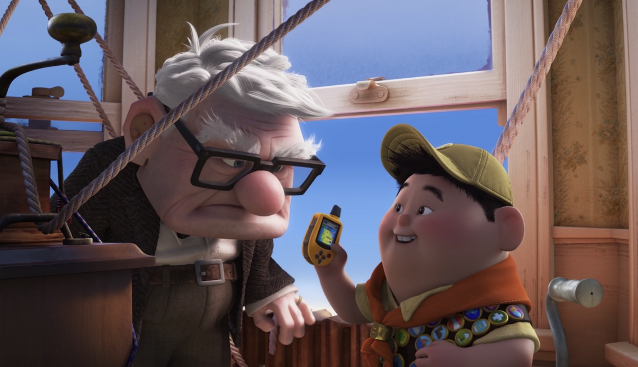 Russell holds up a walkie talkie and smiles while Carl looks down at him, angry