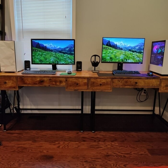 Two writing desks side by side with computer monitors on top