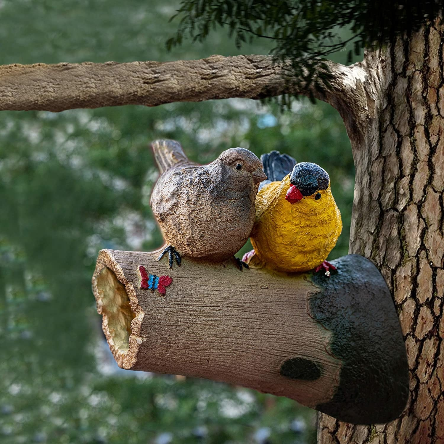 A garden decoration of two birds sitting on a branch.