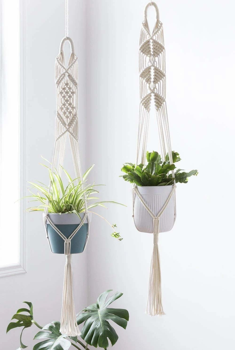 2 hanging macrame plant holders carrying two pots.