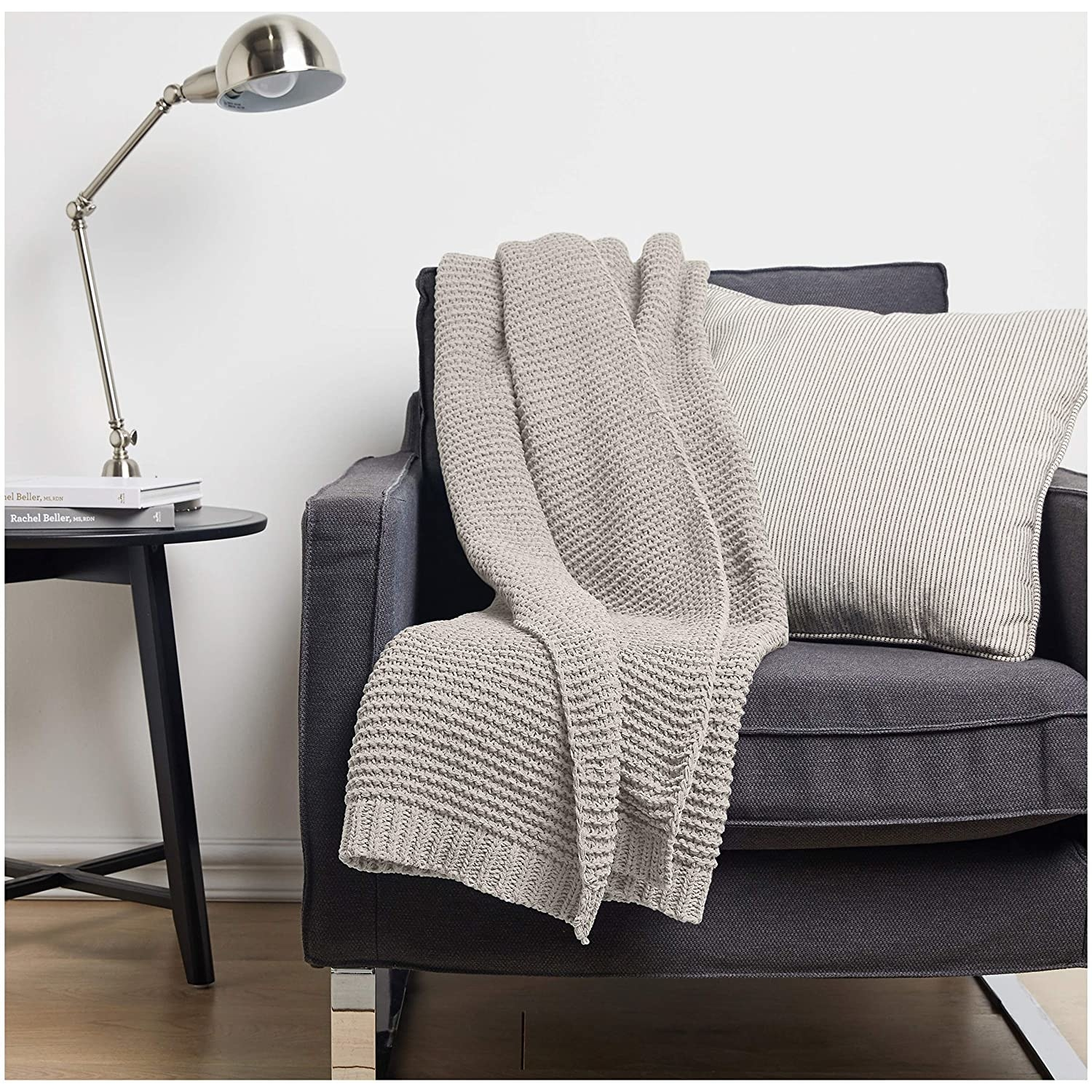 .A knitted grey throw blanket draped over a couch seat,