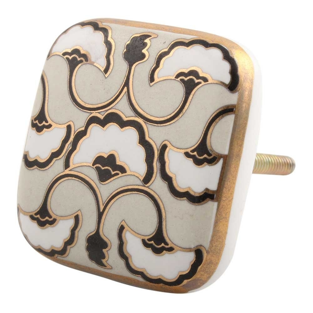A white knob with a black and white floral design and gold accents.