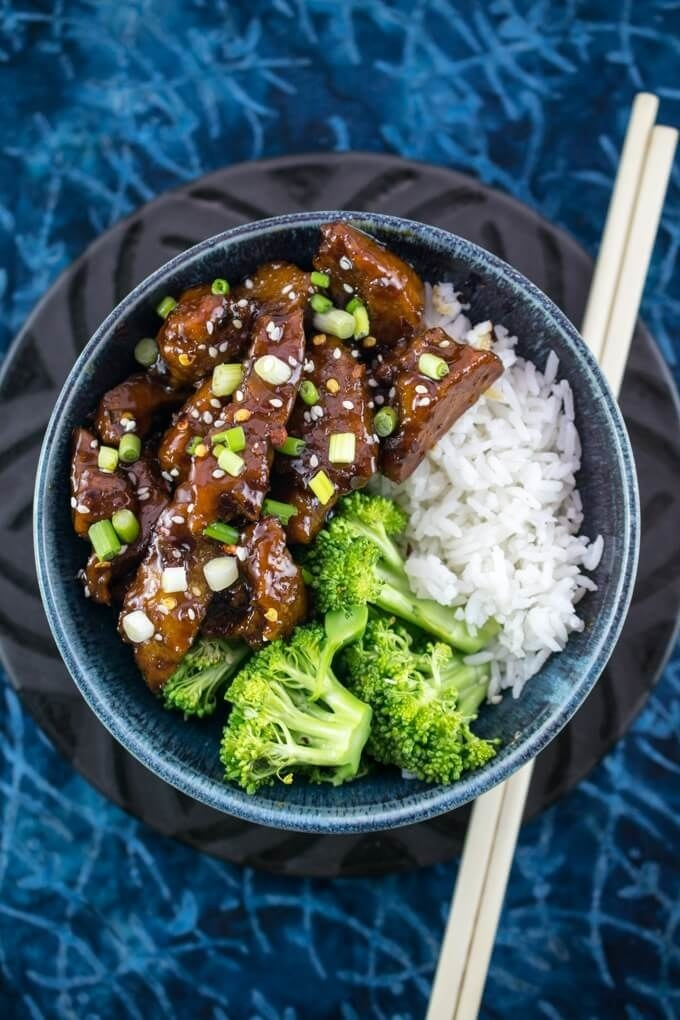 Bowl of sticky, sweet Mongolian seitan and broccoli, with serving of white rice.