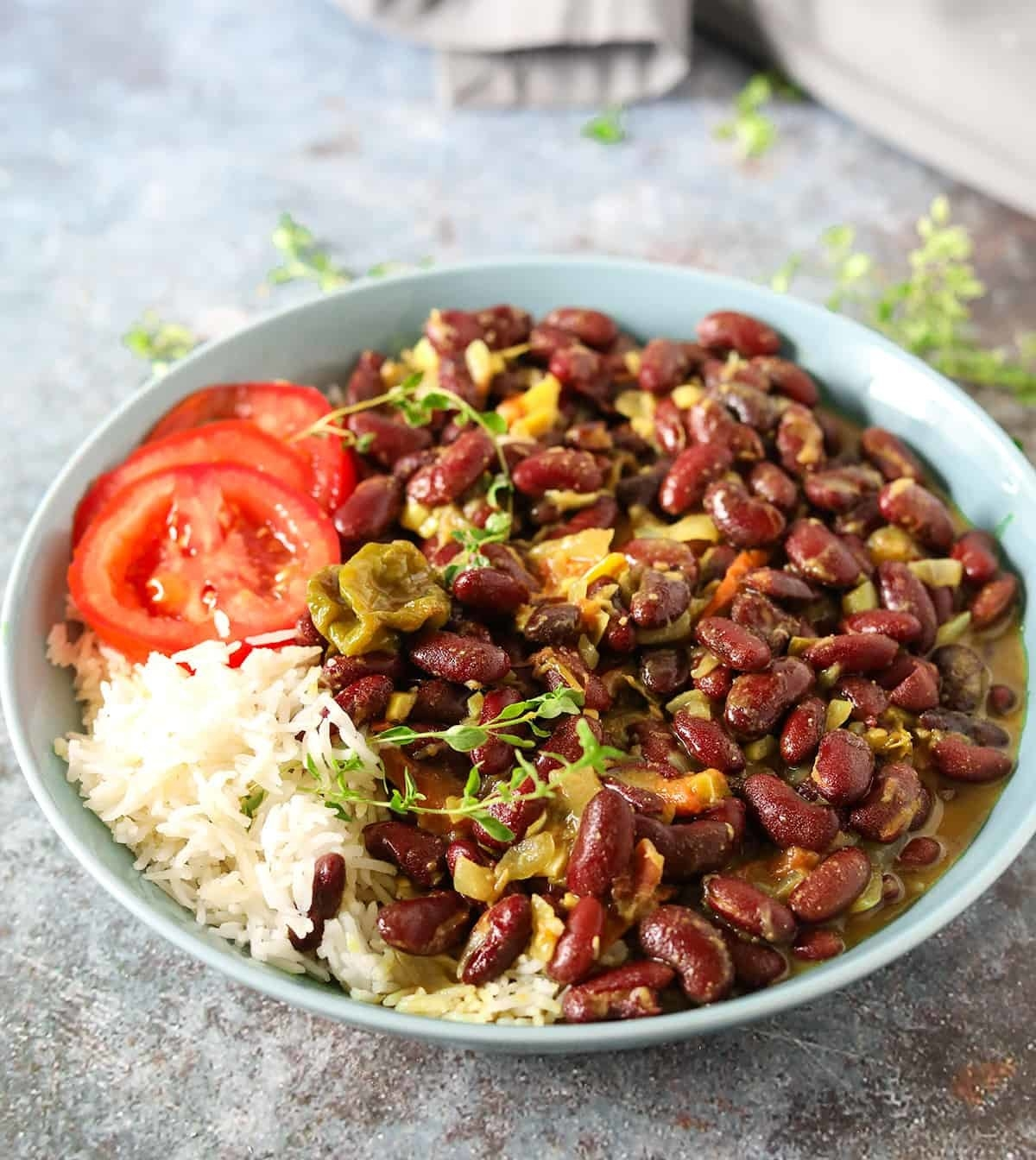 Large plate filled with kidney bean curry, white rice, and tomato slices.