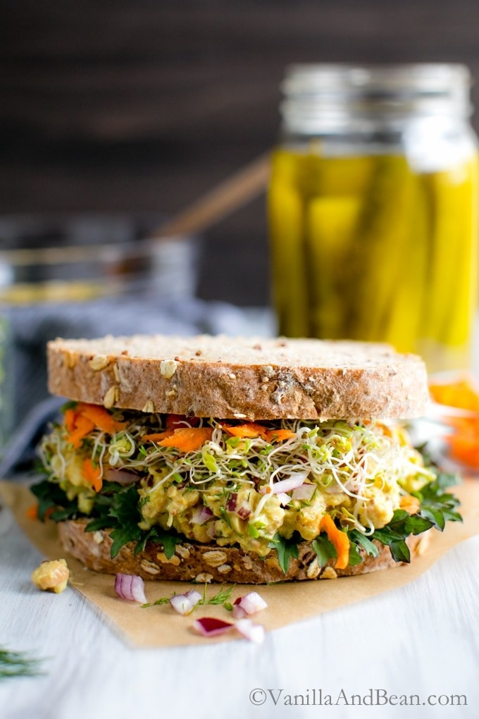A large grainy sandwiched is filled with sprouts and smashed chickpea salad.