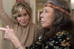 Grace Hansen leans against a wall with one arm while Frankie Bergstein shoots the finger guns with both eyes closed.