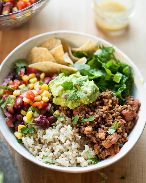 A bowl filled with equal parts rice, lentil walnut taco meat, a corn salad, tortilla chips, and guacamole.