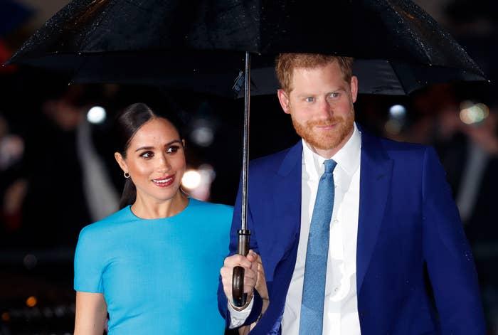 Meghan Markle and Prince Harry stand beneath an umbrella