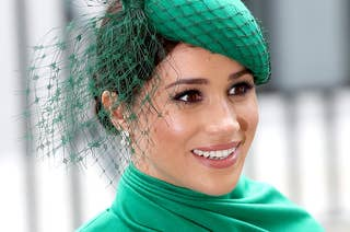 Meghan Markle is photographed smiling and wearing a green hat