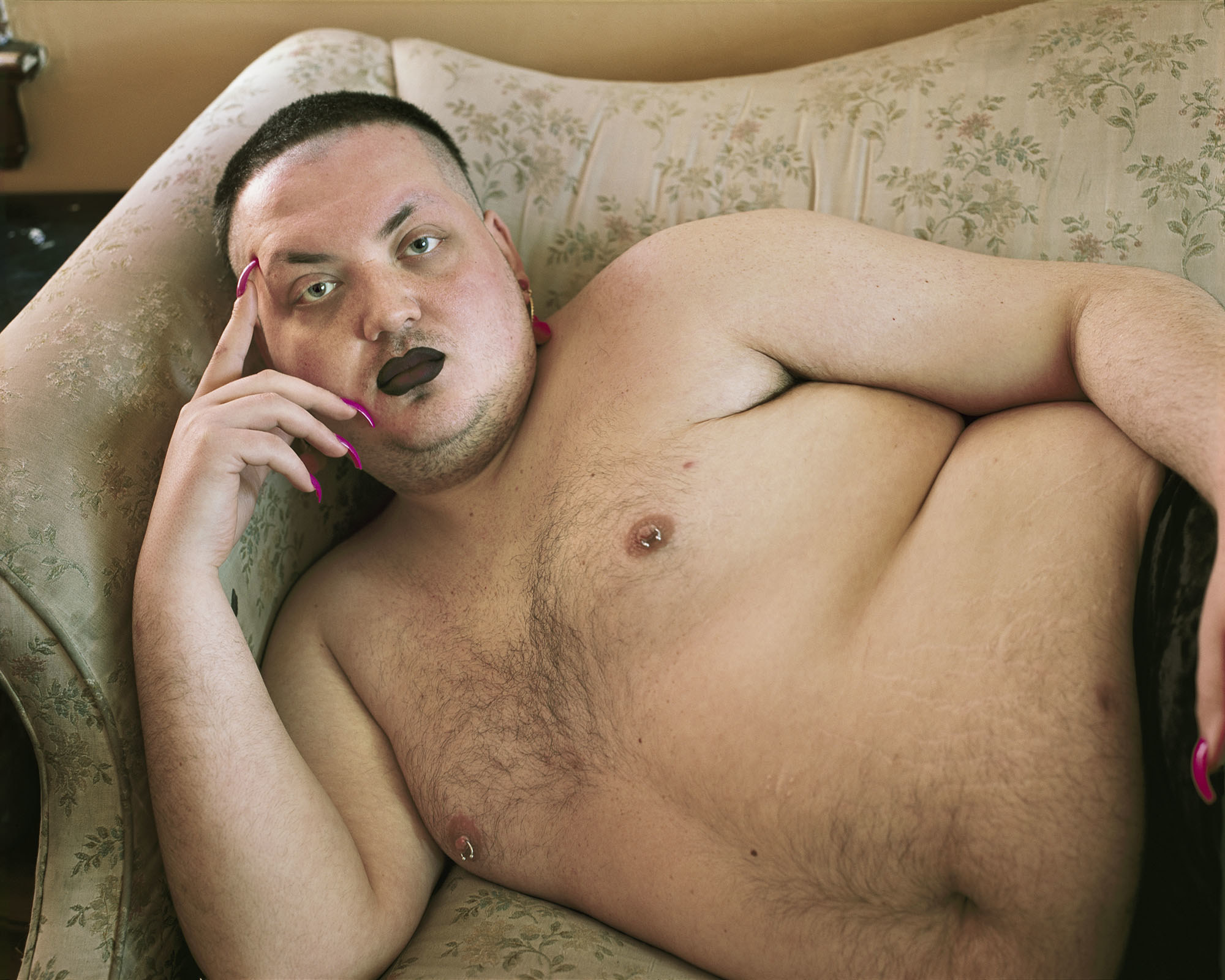 A man with pink nails and black lipstick lounges topless on a couch