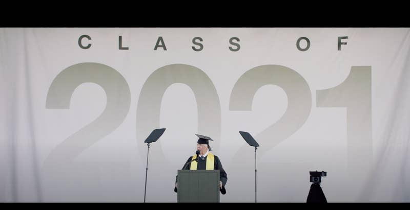 Keene in a cap and gown is addressing a crowd in front of a Class of 2021 sign