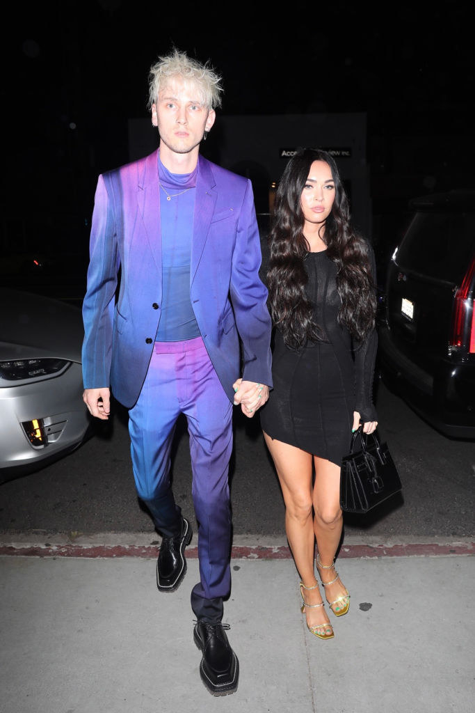 His suit is the colors of the night sky, and her dress is timeless