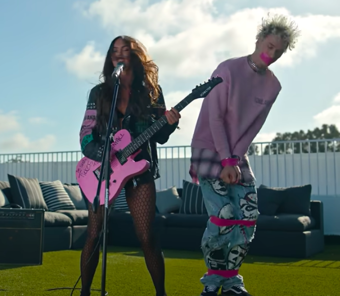 Megan at the microphone, with fishnet tights and holding a pink guitar, and MGK standing next to her with his ankles, knees, and wrists tied up with pink tape