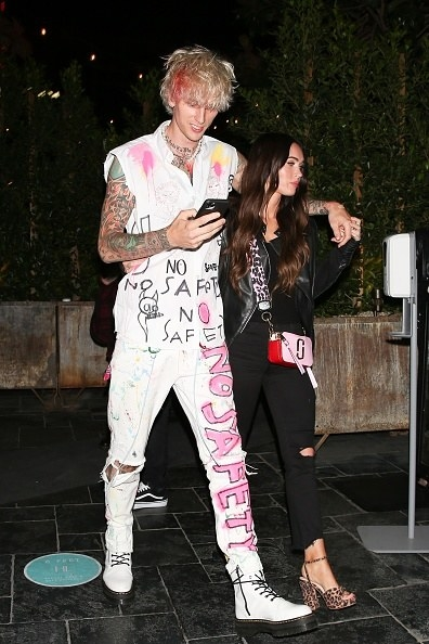 His outfit is covered in graffiti, and hers is classic but edgy