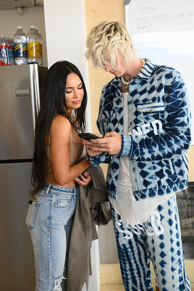 She's wearing another crop top and jeans, while he has geometric-patterned acid wash denim