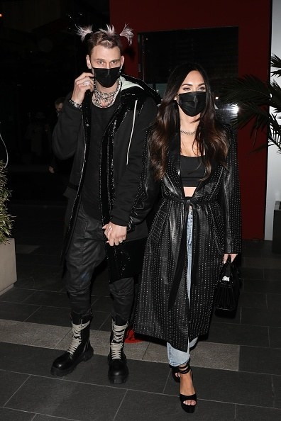 He's wearing all black, and she has a dark coat over a crop top and jeans