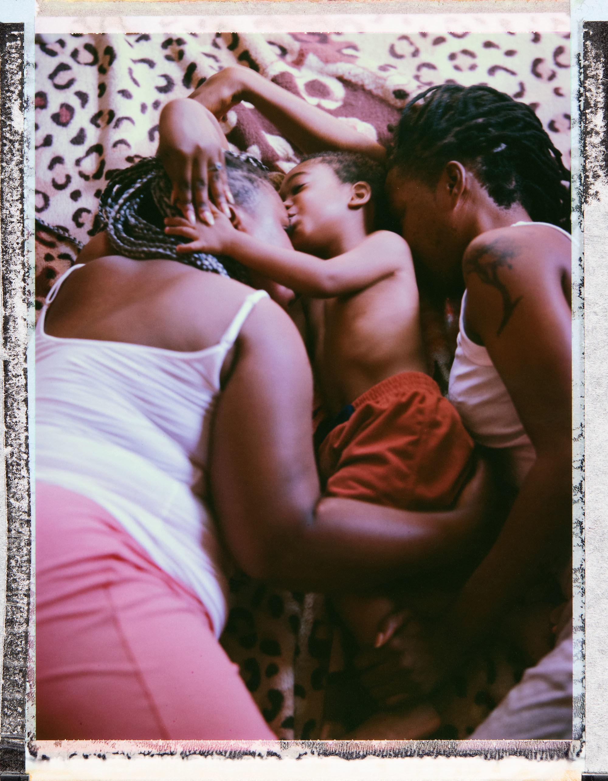 Two women hug a young boy lying down between them