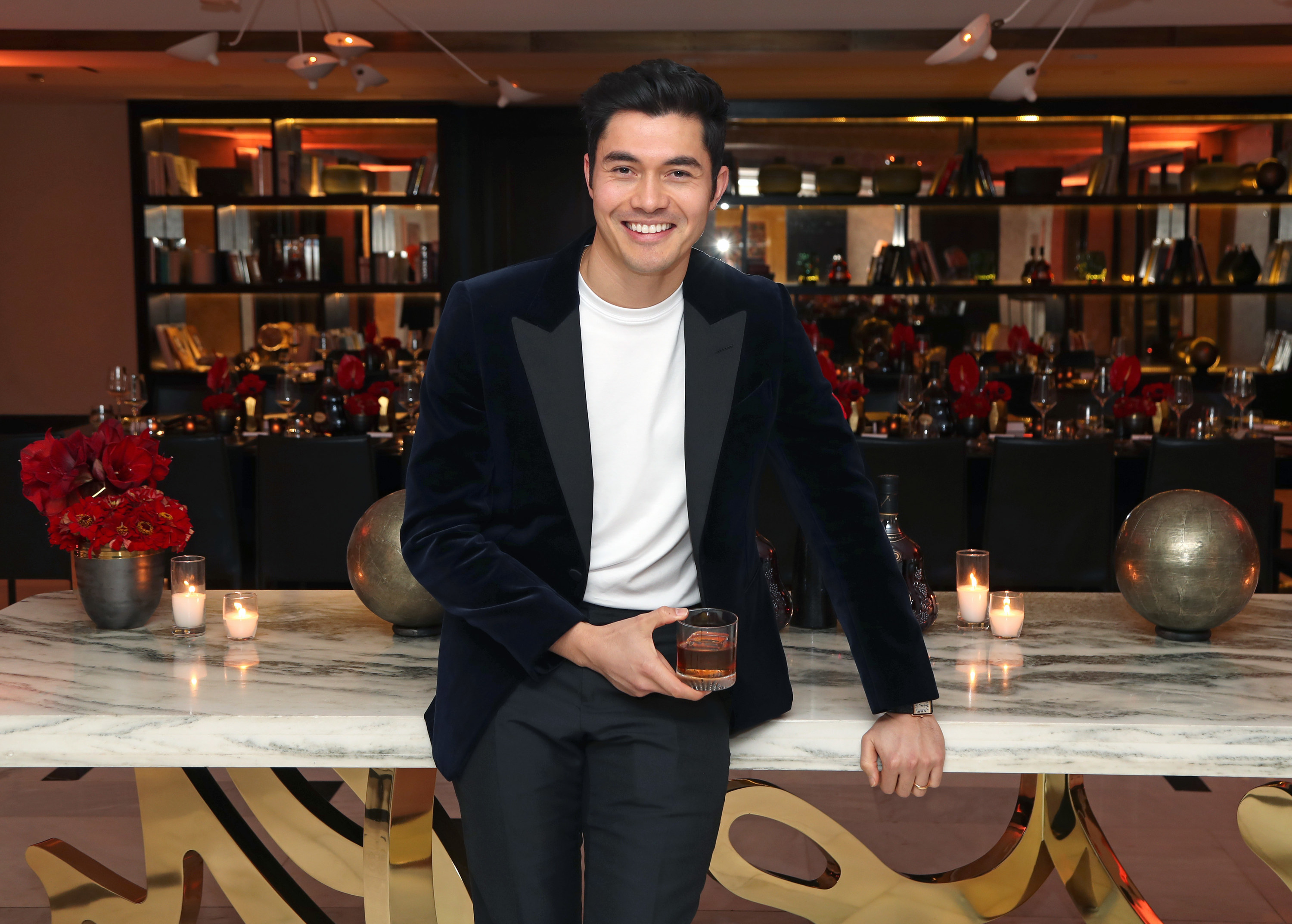 Henry Golding smiles while holding a glass of Hennessy