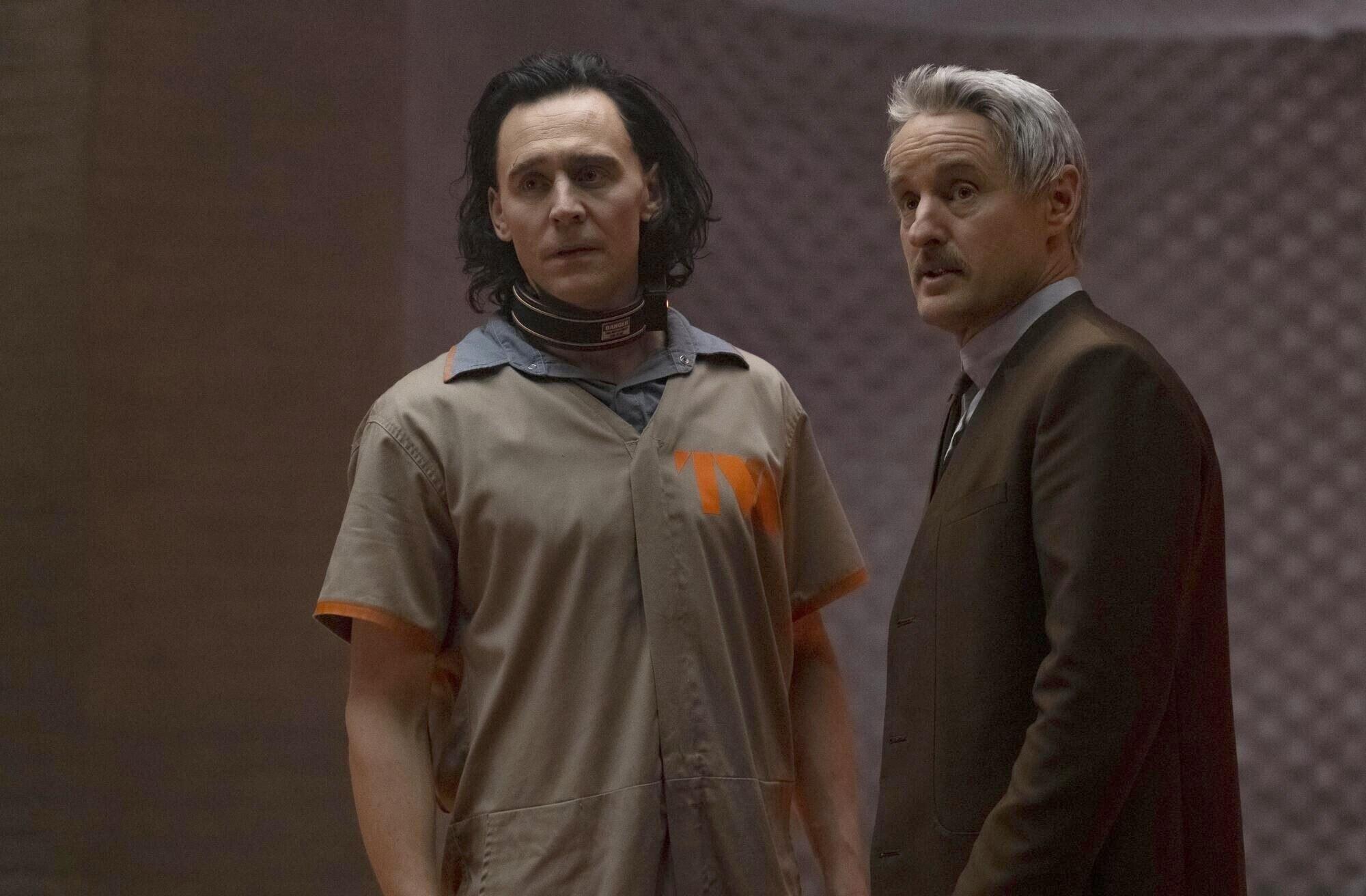 Loki stands in a prison jumpsuit next to Owen Wilson