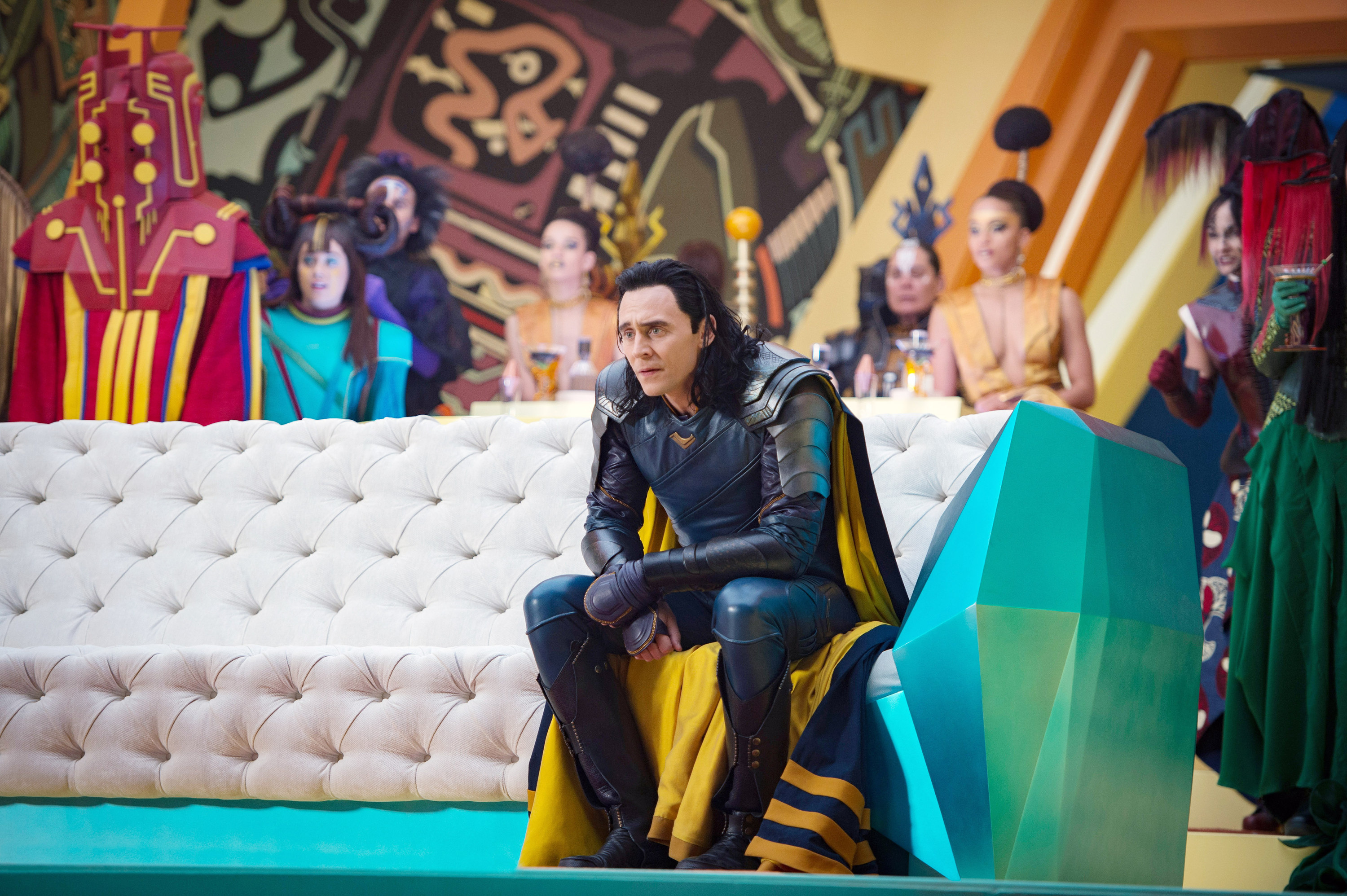 Loki sitting on a couch in a blue outfit