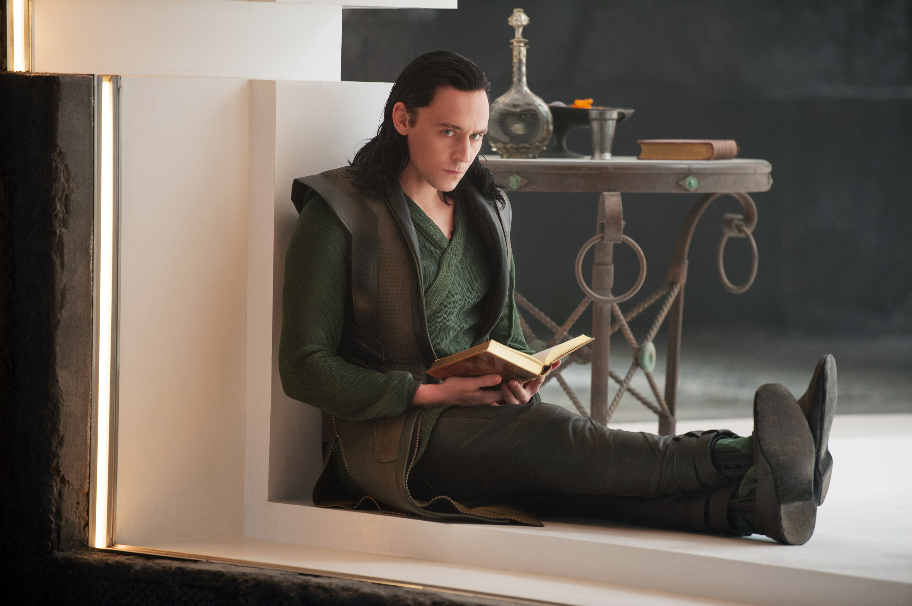 Loki reading in his prison cell