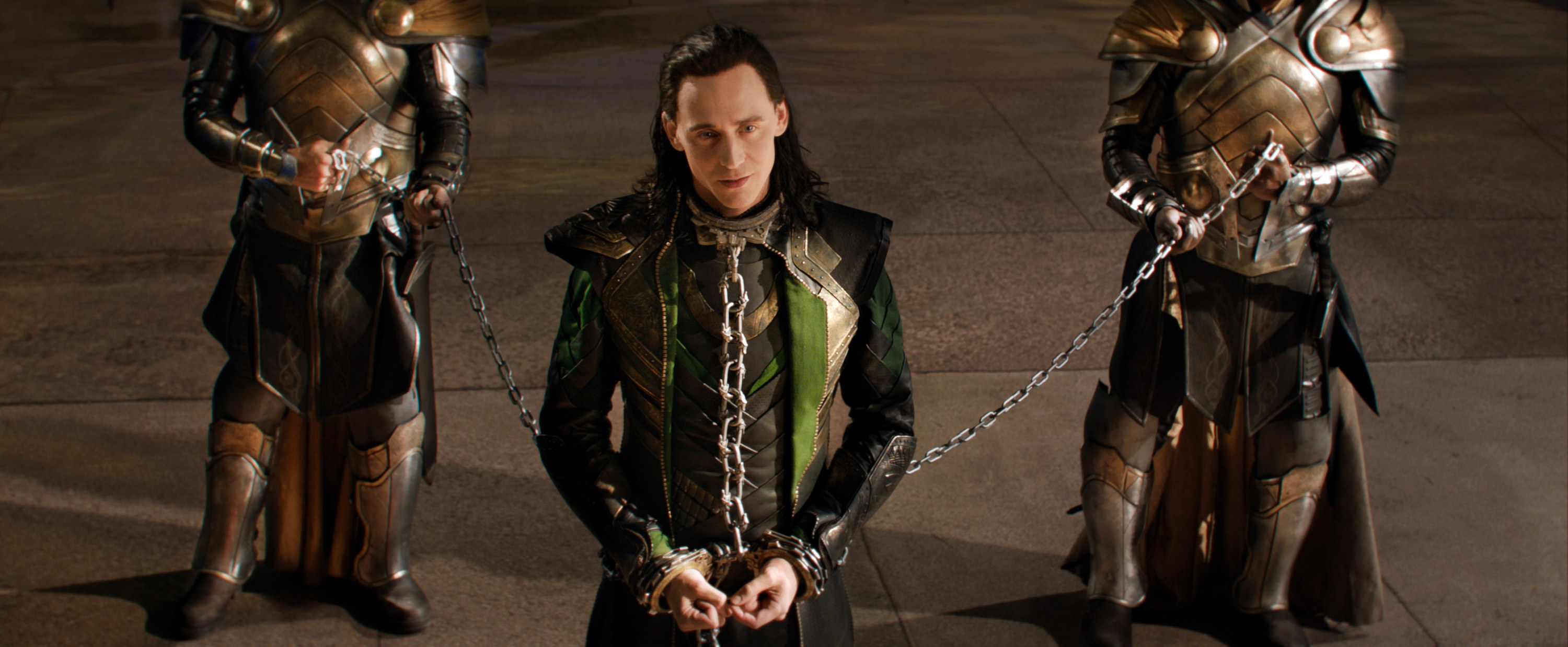 Loki standing in a throne room chained to two guards