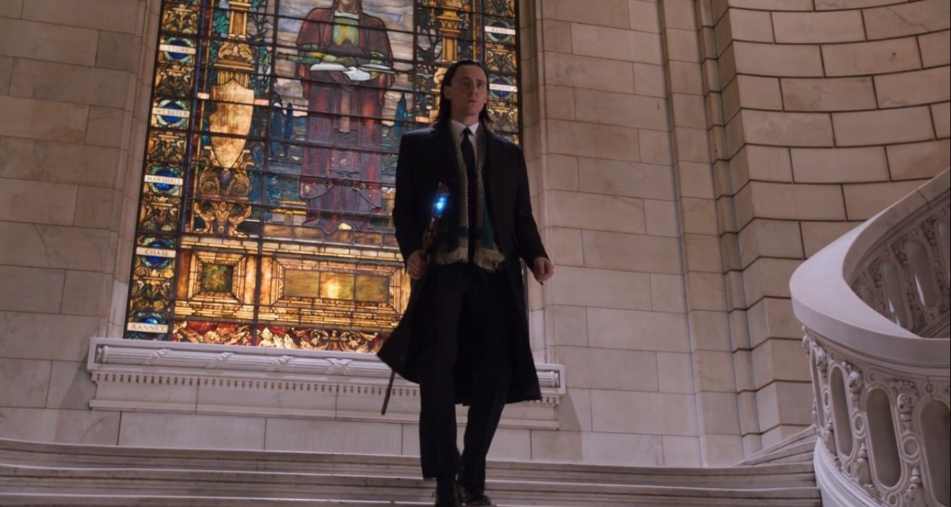 Loki walking down a flight of stairs with a magical staff