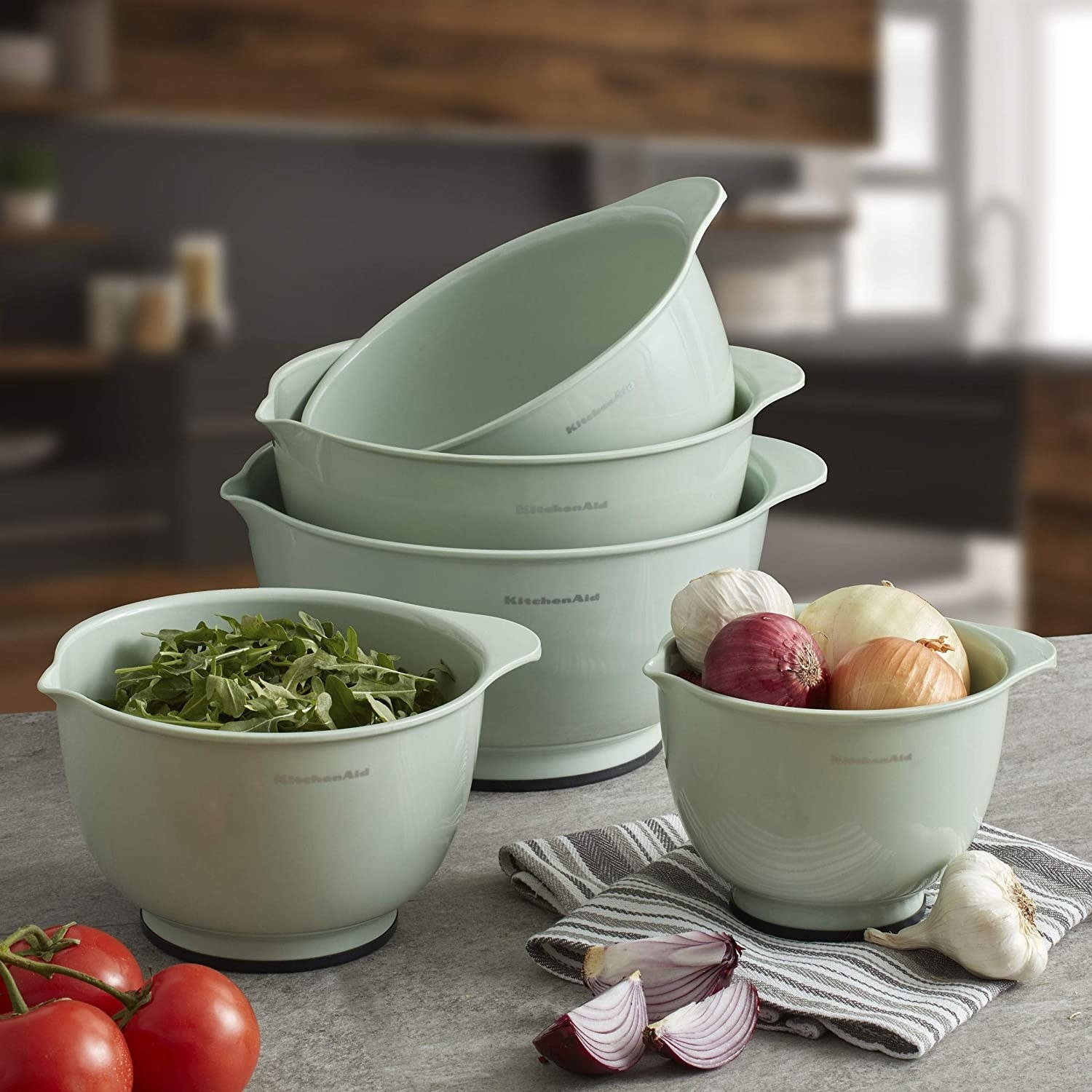 five kitchenaid mixing bowls with food in them
