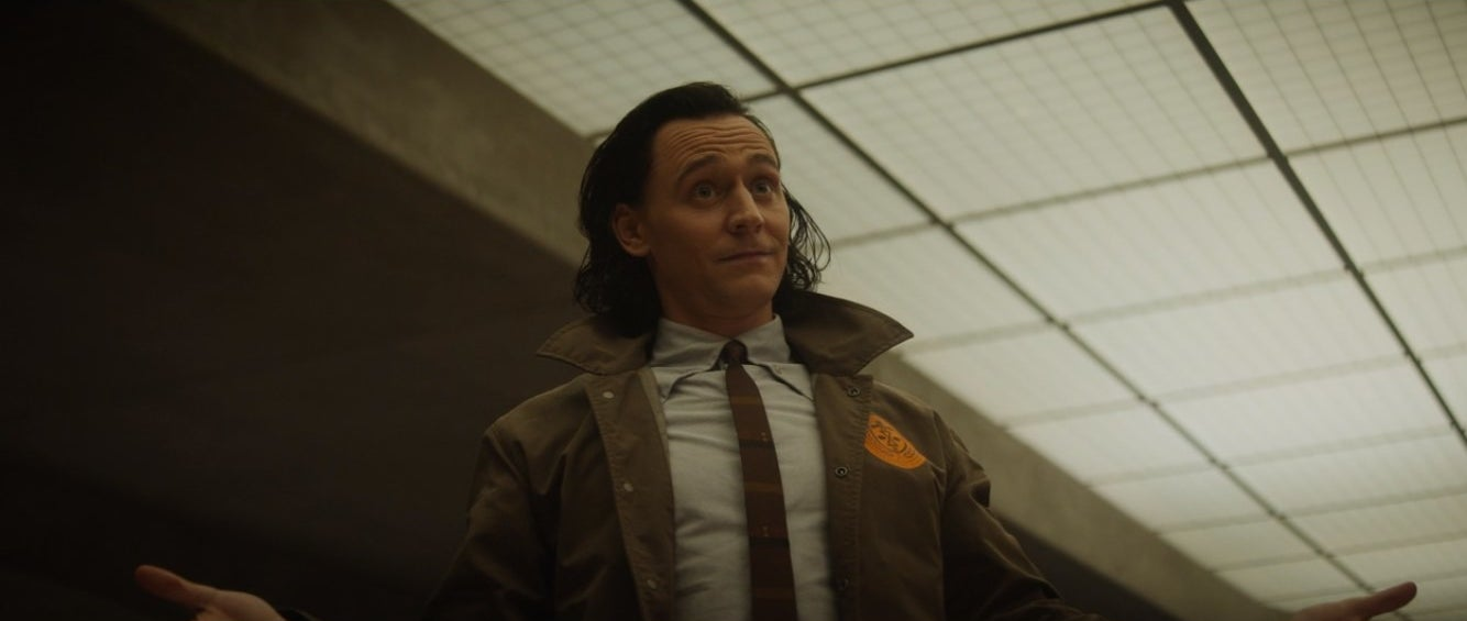 Loki in a dress shirt, tie, and jacket from the 70's