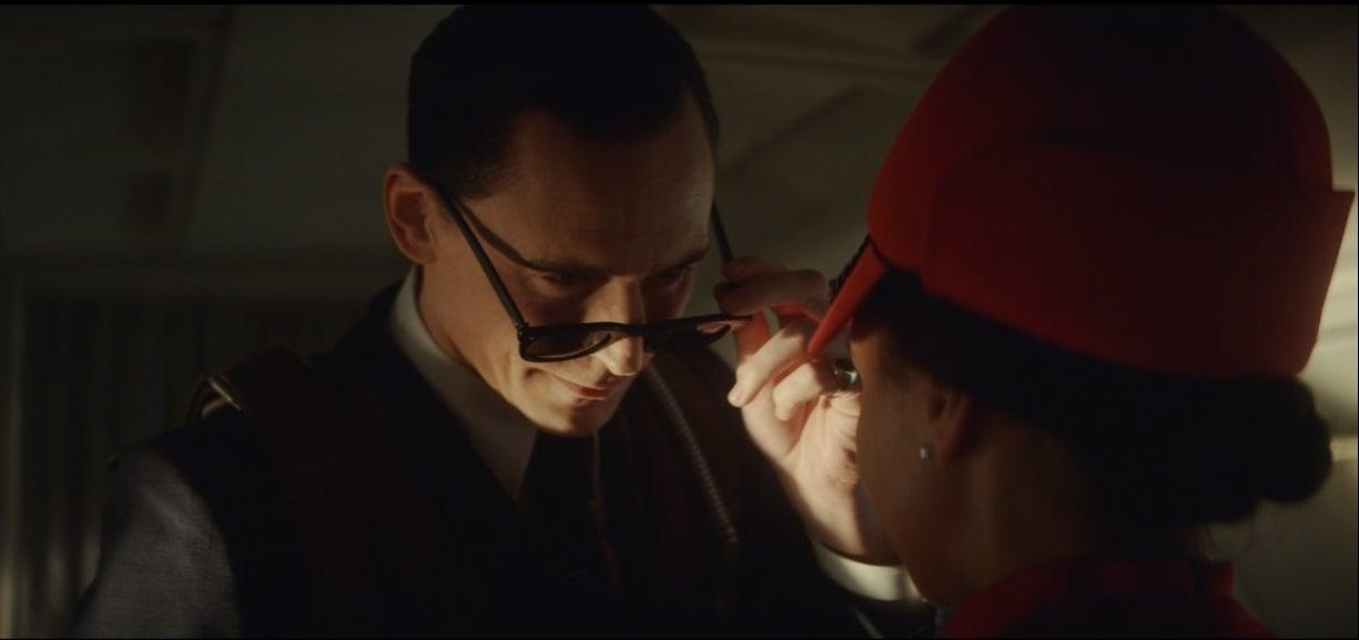 Loki looks over his sunglasses at a flight attendant