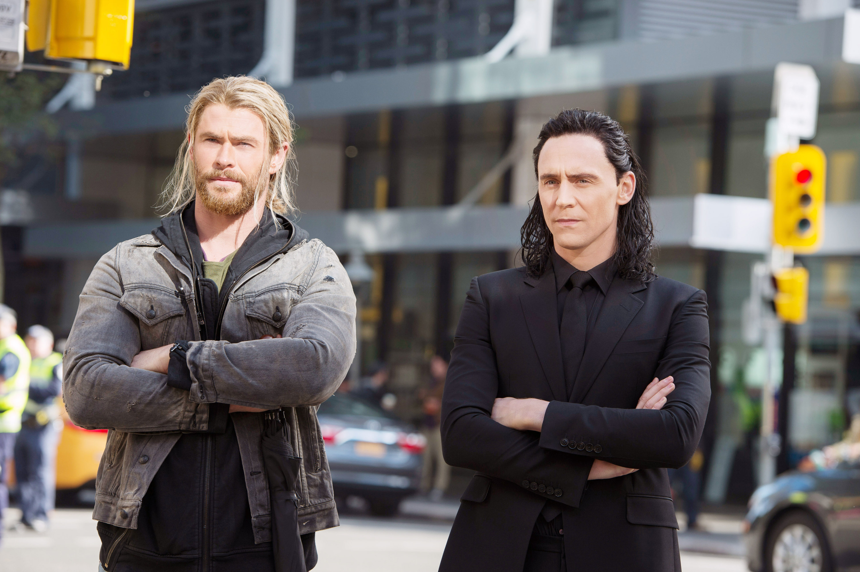 Loki and Thor stand together with arms crossed on a street