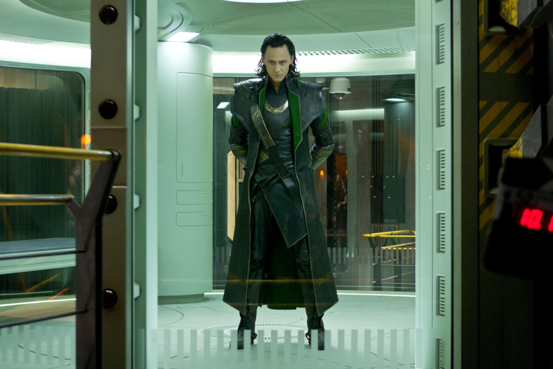 Loki in a prison cell in a long green cloak