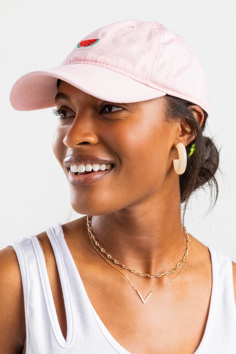 model wearing pink baseball cap with embroidered watermelon