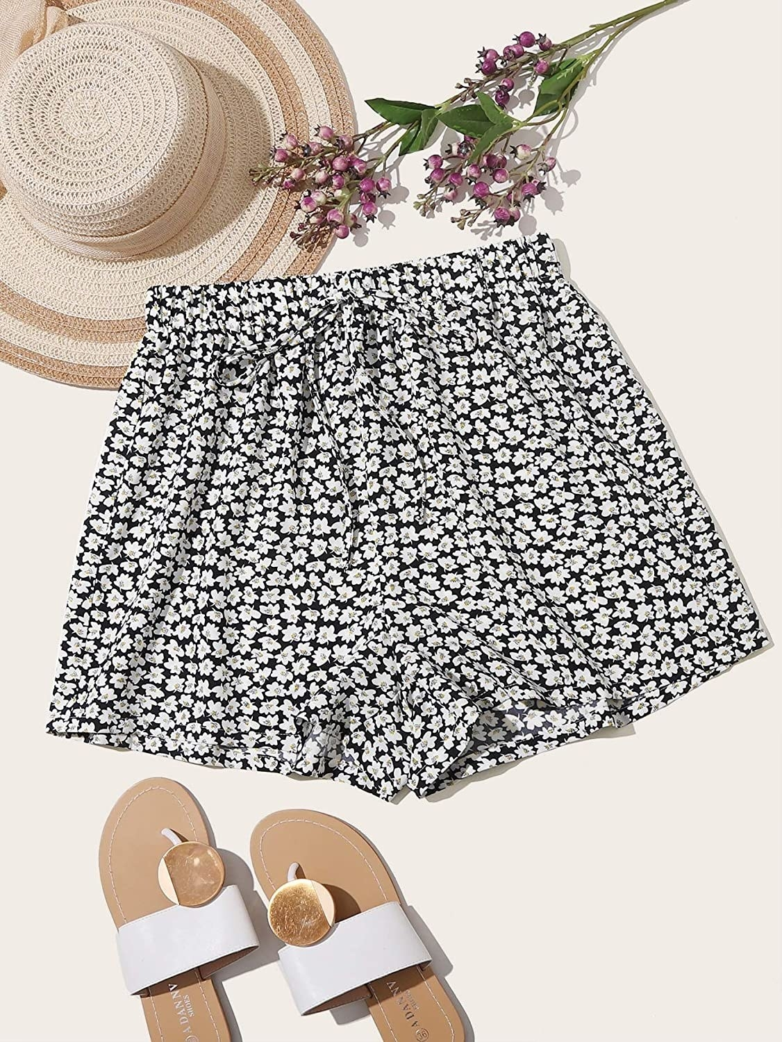 floral shorts next to a pair of sandals, a hat, and some flowers
