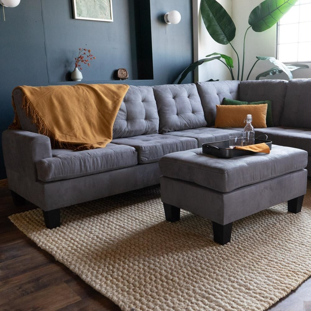 lifestyle photo of the couch in dark gray with mustard-colored blanket and throw pillows on it