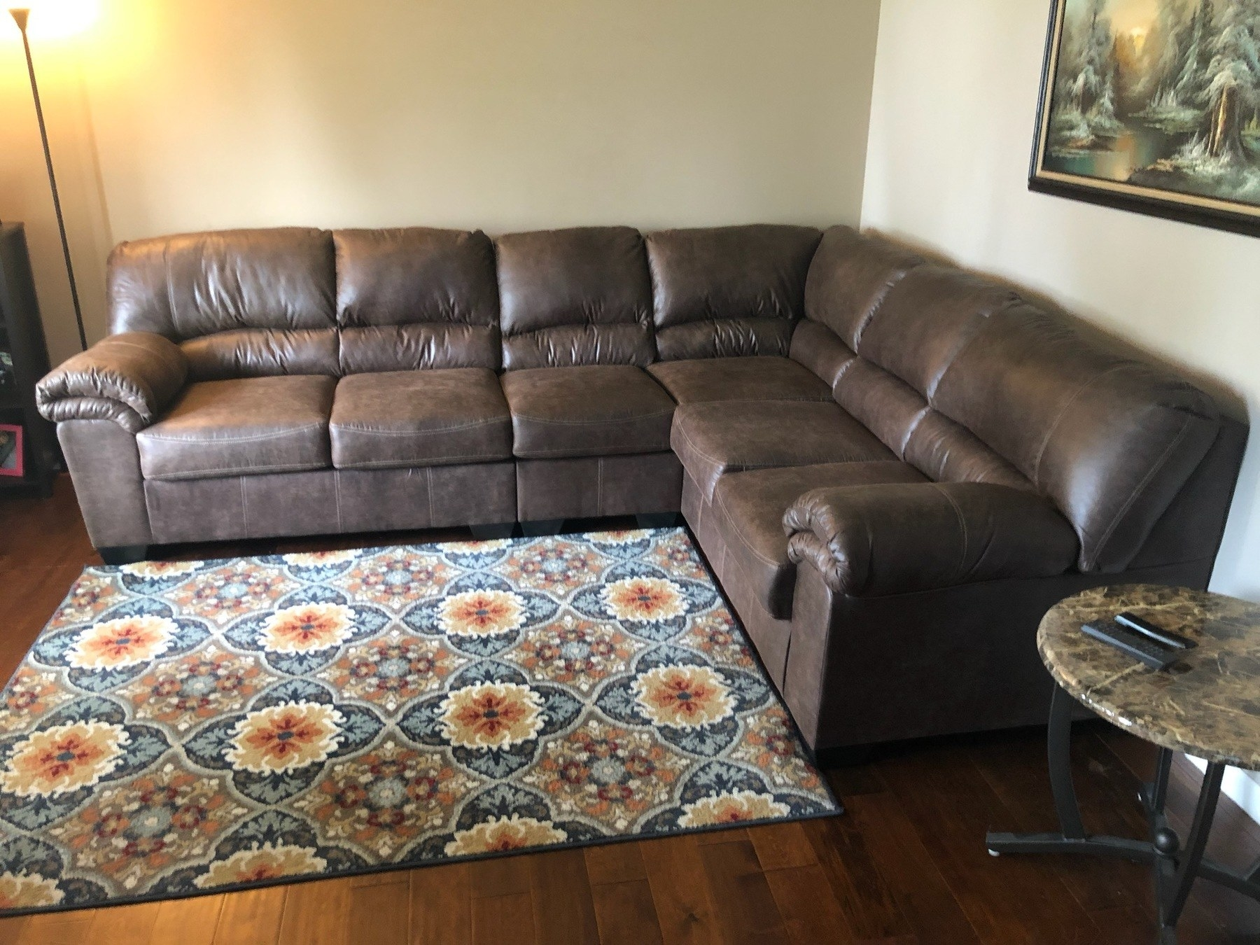 reviewer photo of the couch in the corner of a family room with lamp and floral rug