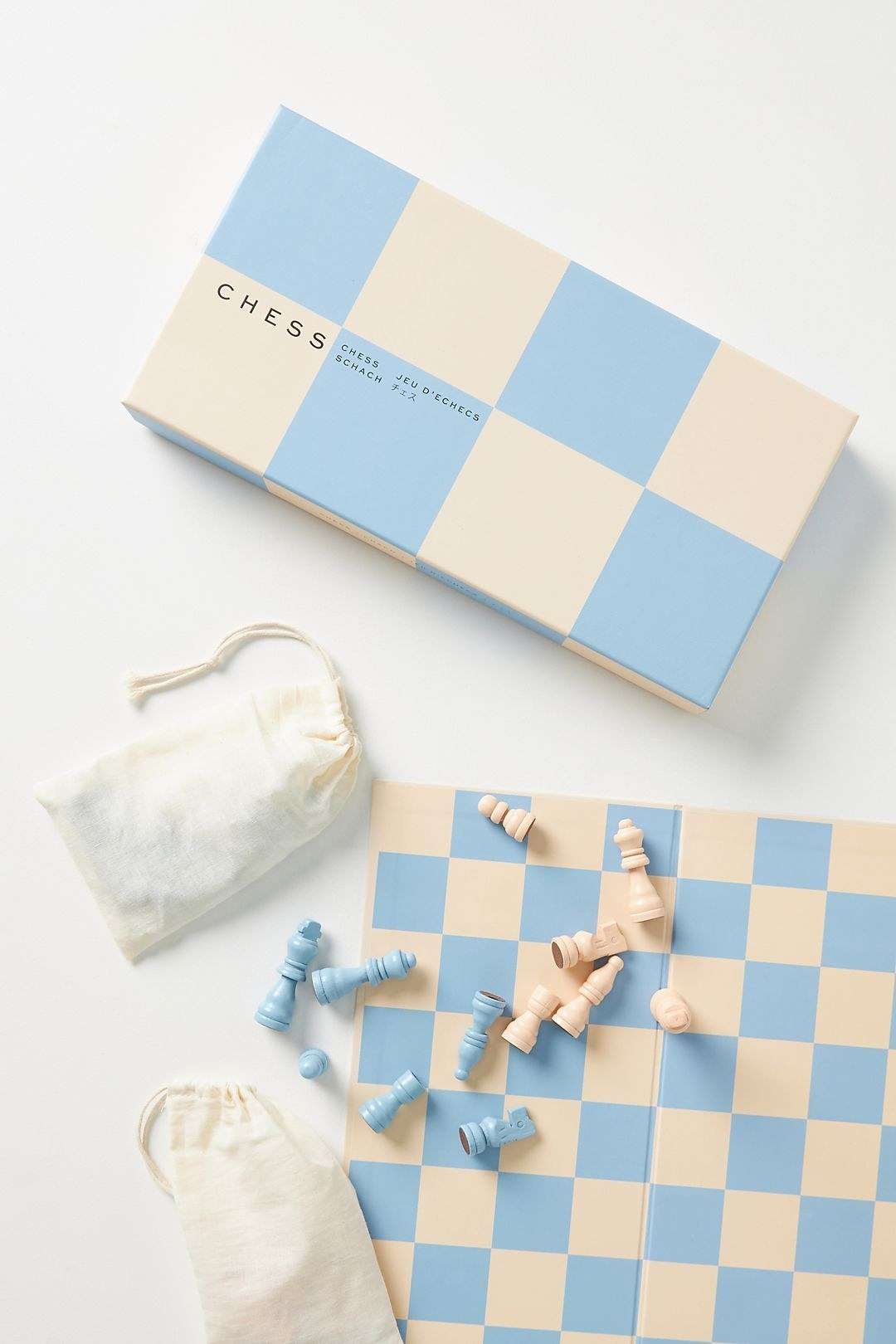 the box, board, and bags for the chess set with the blue and white pieces tossed around