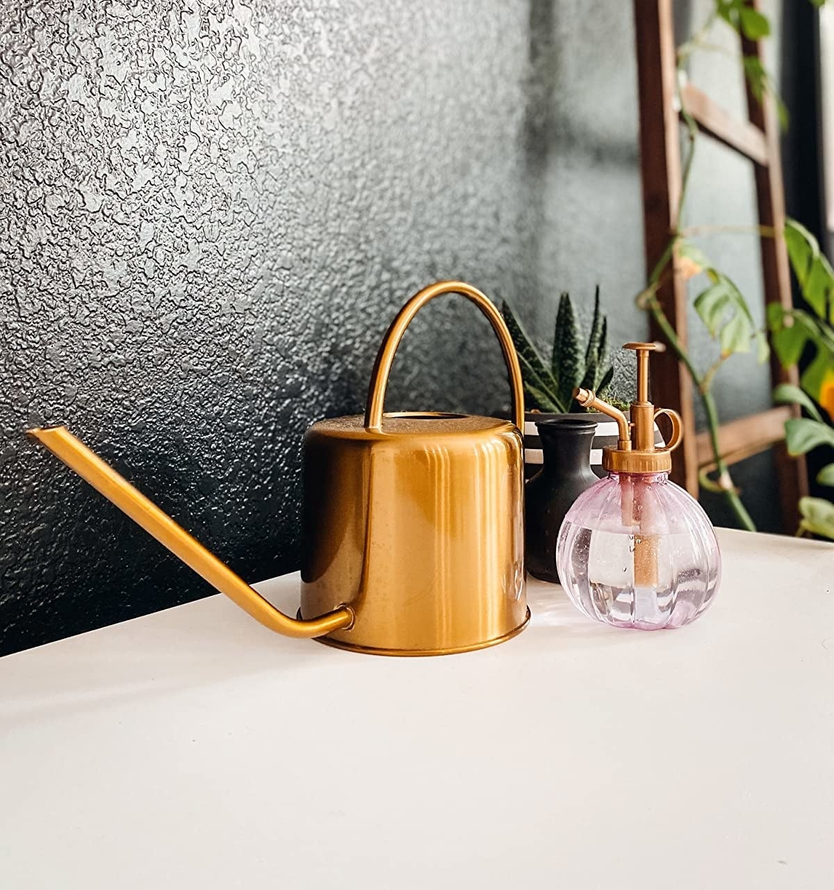 reviewer showing the gold watering can next to the matching mister