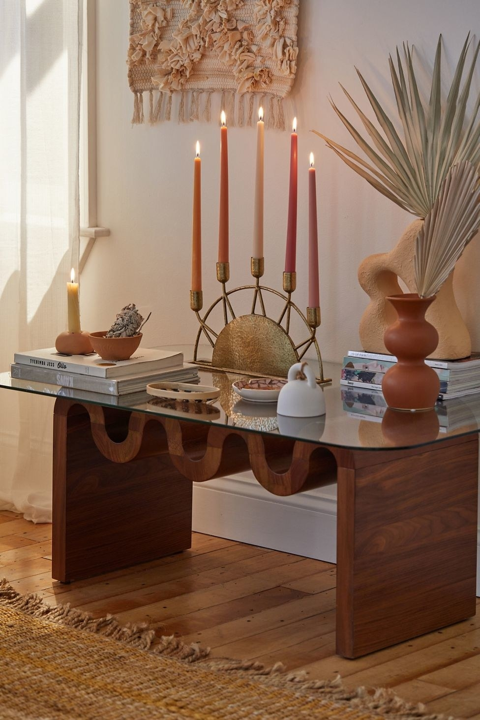 gold candelabra sitting on a table with pink and orange lit candles in it