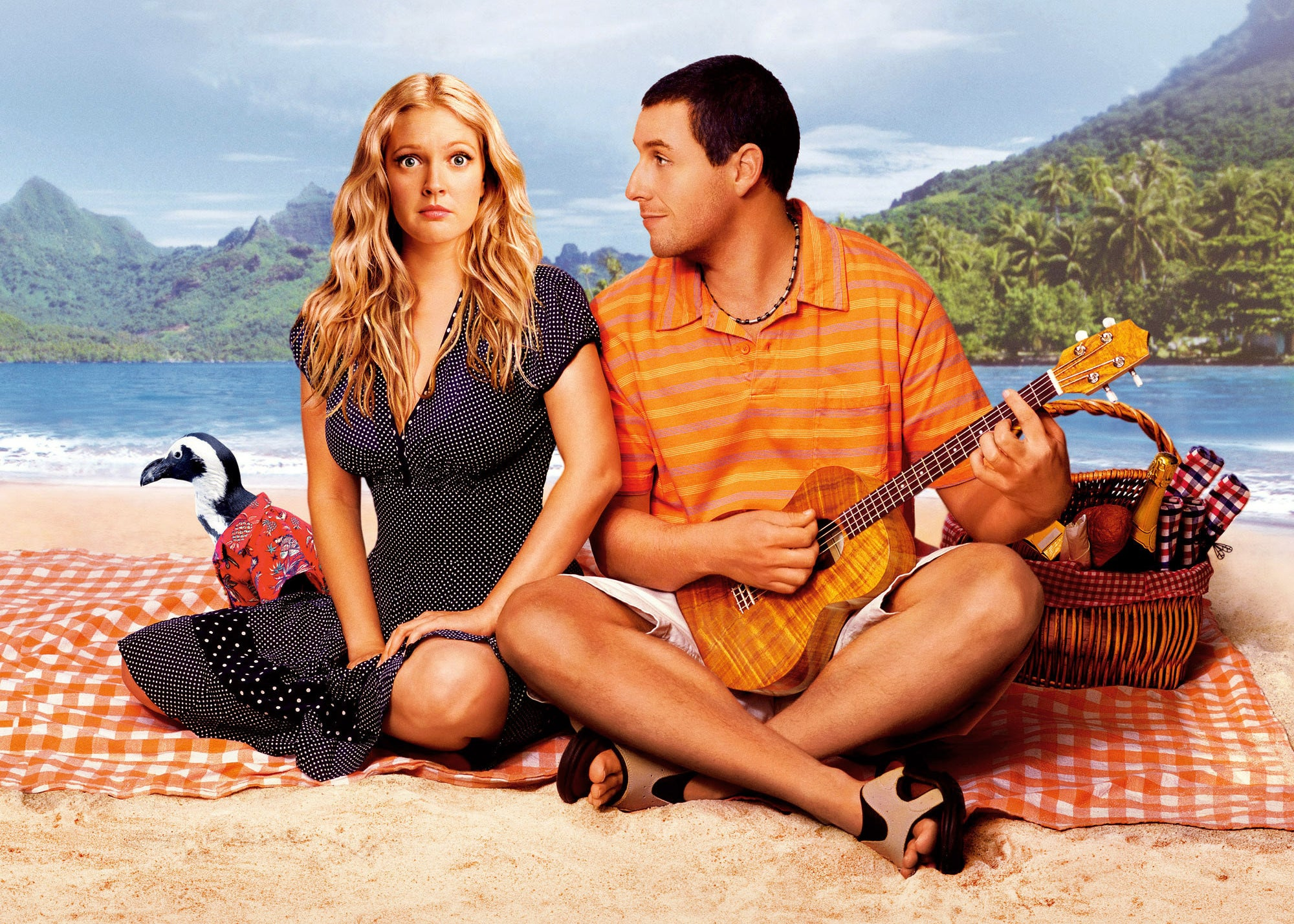 Drew Barrymore and Adam Sandler sit on a blanket on the sand on a beach
