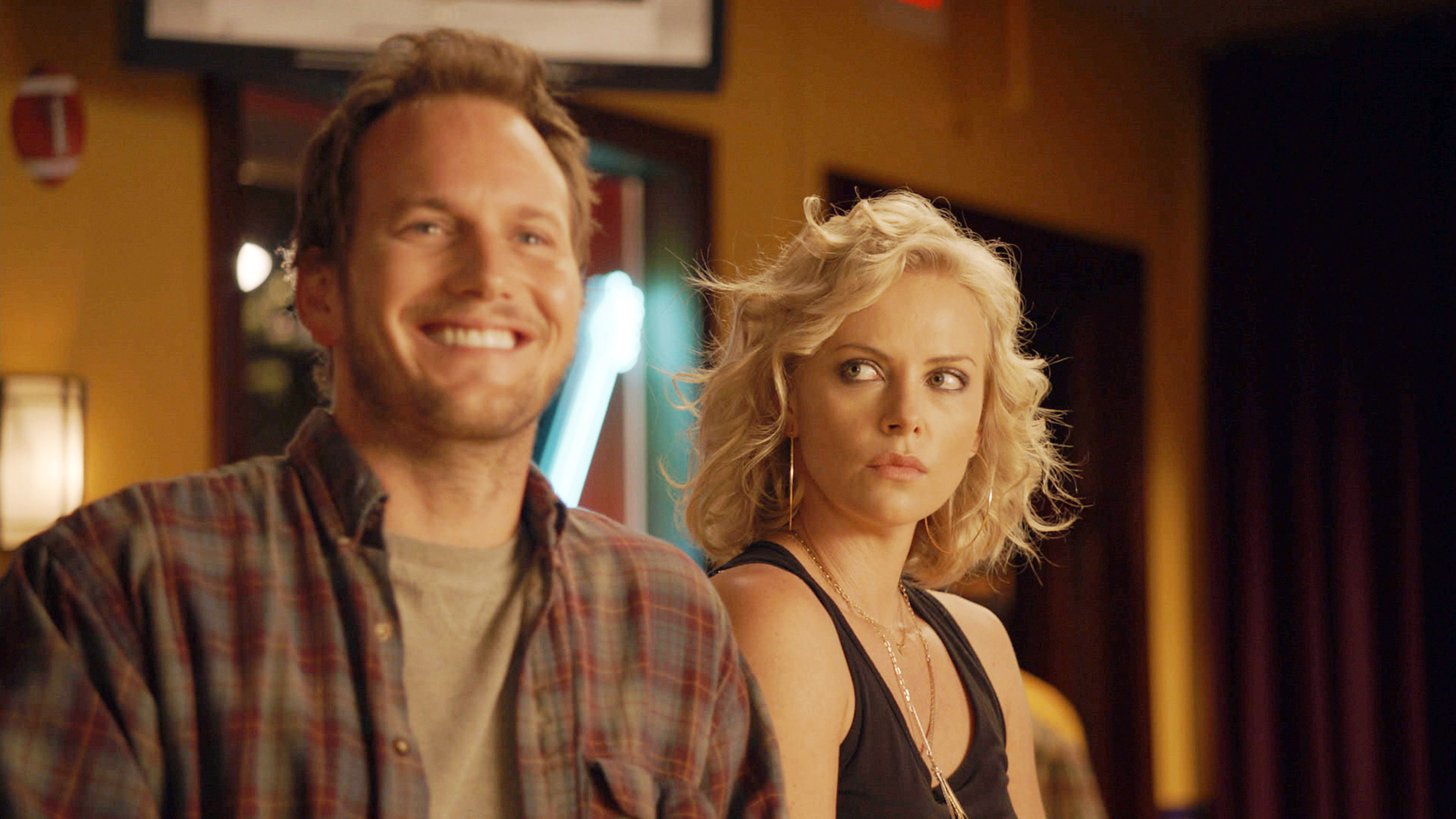 Patrick Wilson smiling and Charlize Theron looking at him and not smiling