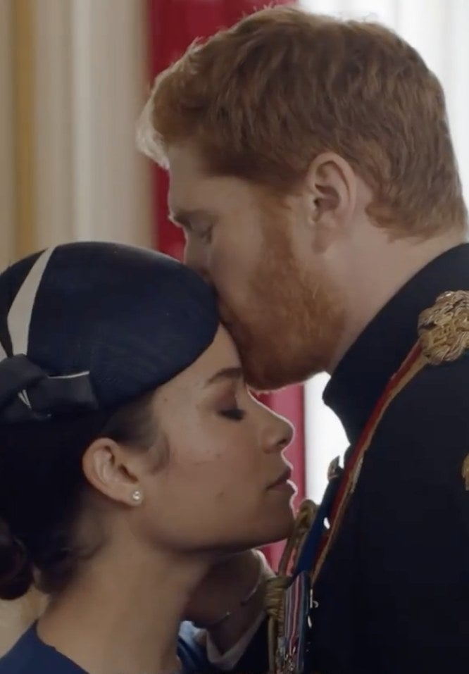 A screenshot from the movie where Harry kisses Meghan's head