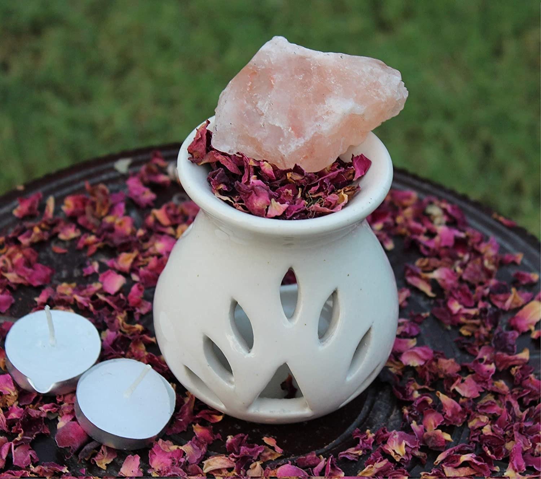 A white ceramic aroma burner with rose petals, Himalayan rock salt, and two tea light candles