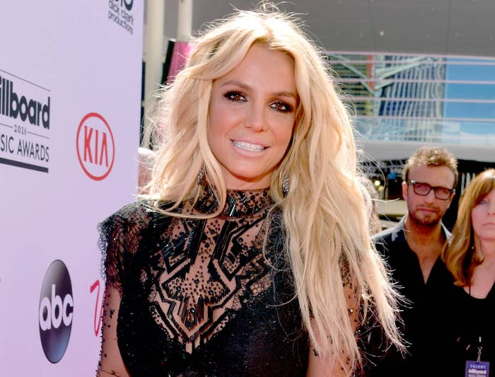 Britney smiles in a black dress with sheer long sleeves